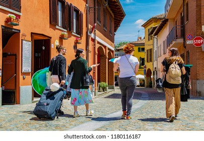 """BAROLO, CUNEO, PIEDMONT, ITALY - June 9, 2018: Street view with people during the """"Barolo Fashion Show"""" day. The area called Langhe is a World Heritage Site."""