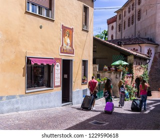 Barolo, Italy - May 24, 2018: Street with tourists, a wine shop, and castle in the background. Barolo is the capital of Langhe (Unesco World Heritage Site), where Barolo wine is produced.