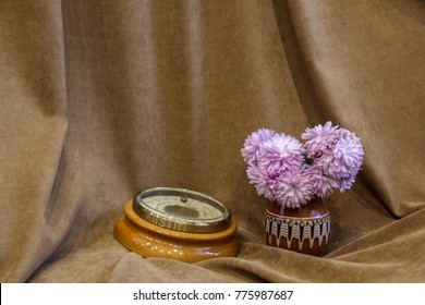 Barometer next to the purple chrysanthemums. Flowers and appliance. Brown background. Chrysanthemums in a vase.