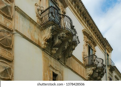 Baroque Balcony with Stone Shelves and Parapets in Wrought Iron. Richly Decorated Windows Stand Out on a Plastered Façade