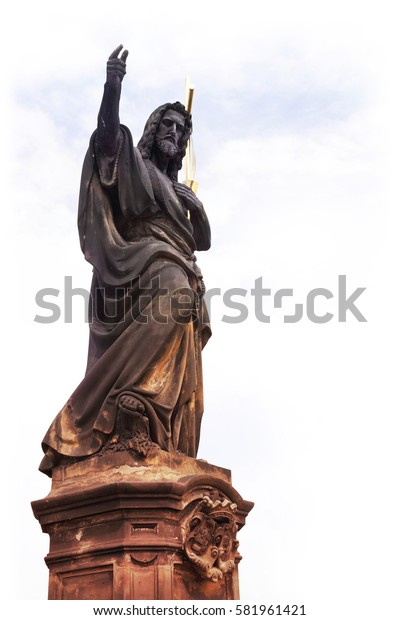 Baroque stone statue of John the Baptist holding a cross and pointing the way on light cloudy background.