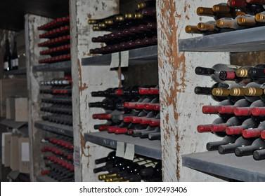 Barossa Valley, South Australia/Australia - January 07.2018: Display of dusty vintage wine bottles in the dark wine cellar.