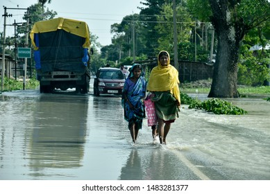 Barpeta, Assam, India. 16 July 2019. People walking wade through flood water after a heavy rainfal in Assam.