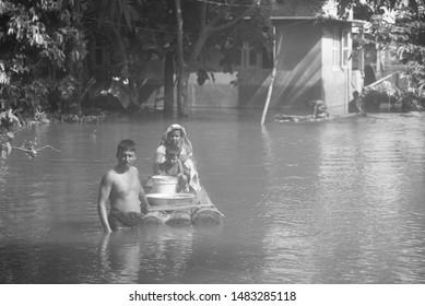 Barpeta, Assam, India. 16 July 2019. Villagers wade through flood water after a heavy rainfall in Assam.
