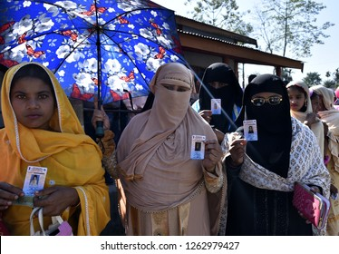 Barpeta, Assam, India. Dec. 09, 2018. Women voter shows her voter ID card while standing in a queue at a polling station during the 2nd phase of the panchayat elections in Barpeta.
