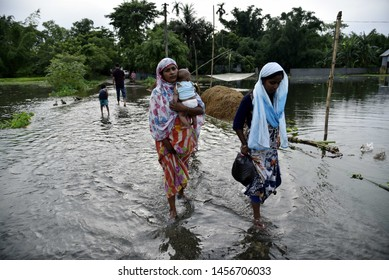 Barpeta, Assam, India. July 12, 2019. People wade through flooded road  at flood effected Kalgachi in Barpeta.