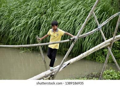 Barpeta, Assam, India. May 3, 2019.  Children crossing a bamboo bridge  at kayakuchi village in Barpeta district of Assam.