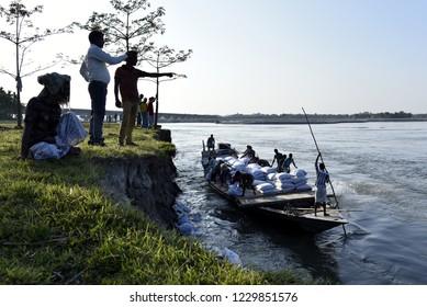 Barpeta, Assam, India , Nov 13, 2018.  Public Works Department (PWD) of Assam labourer throwing sand bag from boat in the banks of Beki River  to reduce soil erosion.