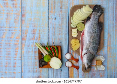 Barramundi or asian seabass fish with salt, msg,ginger,garlic,onion,key lime, chilies and lemongrass over the wooden cutting board.