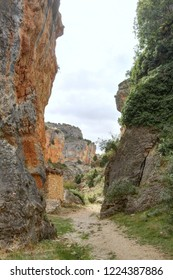The Barranco de la Hoz Seca (Dry Defile Gully) canyon, with scarps, bushes and red rocks, in a cloudy atumn, in the Jaraba rural town, Aragon, Spain