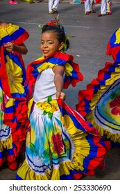 BARRANQUILLA, COLOMBIA - FEBRUARY 15, 2015: Performers with colorful and elaborate costumes participate in the Great Parade of Carnaval, Happy young girl smiling in traditional Colombian colors dress