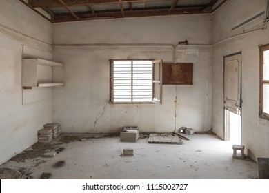 A barred window with broken glass stands open in the wall of a room in an abandoned, derelict building with dirt and building materials on the floor and stained, cracked walls.