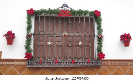 Barred window decorated with garland and Christmas message above tiled wall in Andalusian village street