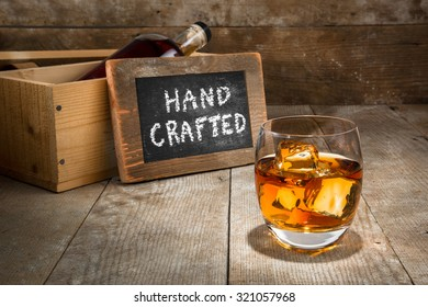 Barrel aged craft liquor spirits glass ice bourbon whisky scotch brandy rum on wood bar table whiskey