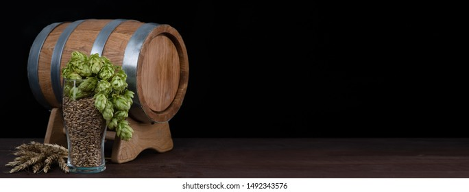 Barrel and beer glasses with wheat and hops on dark wooden table. Empty space for text. Black background