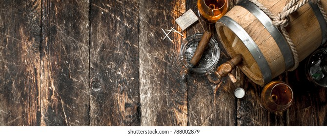 Barrel with French cognac, glasses and a cigar. On a wooden background.