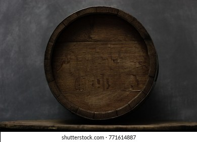 Barrel on an old round wooden table. Beautiful dark background