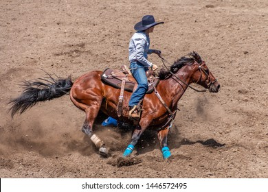 Barrel Racing at a Rodeo, cowgirl riding a roan colored horse around a barrel. She is wearing a large black cowboy hat. The dirt is flying as the horse digs in.