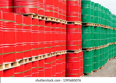 Barrels of 200 liters of metal are in the pallet on the street under the open sky. Red and green barrels two hundred liters for liquid.