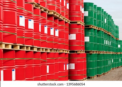 Barrels of 200 liters of metal are in the pallet on the street under the open sky. Red and green barrels for liquids.