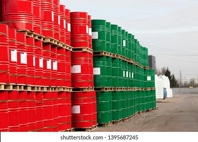Barrels of 200 liters of metal are in the pallet on the street under the open sky. Red and green barrels for petroleum, chemicals, gasoline.