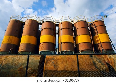 Barrels with fuel against blue sky.