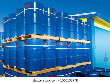 Barrels for loading. Metal drums stand on wooden pallets. Chemicals in the package. Goods of the chemical industry.