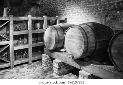 Barrels with a wine in a cellar with a brick wall background. Black and White Photography. Beautiful vintage.