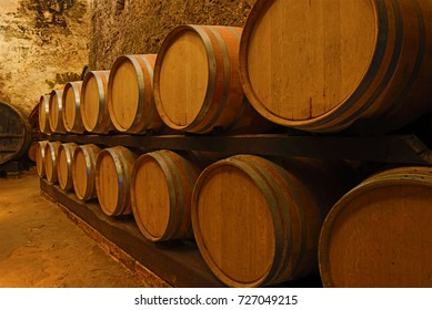 Barrels of young wine in an old wine cellar. Tuscany, Italy