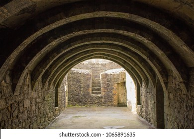 Barrel-Vaulted Basement of Crookston Castle in the Pollock Area in Glasgow, Scotland. Photo Showing Cellar Style Arch Ceiling and Stone Walls. Free Entry to the Publick