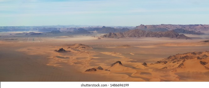 barren desert, dunes in the foreground, plateau and mountains in the background. airport on the left but no real focus point