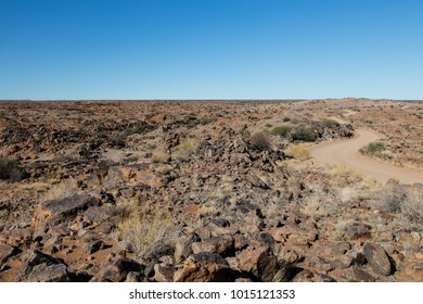 Barren and dry landscape in the Augrabies Falls National Park with a winding dirt road and a clear blue sky
