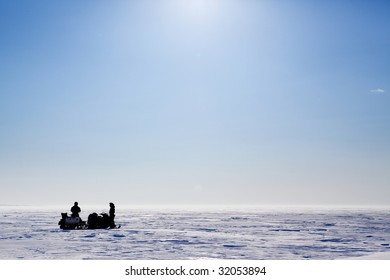 A barren flat winter landscape with two people and snowmobiles