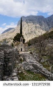Barren landscape with a small abandoned church in the mountains, surrounded by derelict stone walls. St. George Church on St. John Mountain in Kotor, Montenegro.