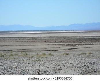 Barren rocky desert landscape with hazy mountains beyond under hazy blue sky.