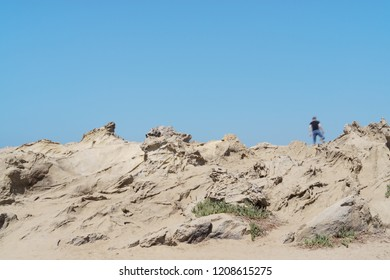 Barren rocky hill edge and clear blue sky. Small rock formations. Copy space.