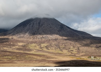 Barren Scottish mountain with the top covered in clouds. Small white house at the bottom.