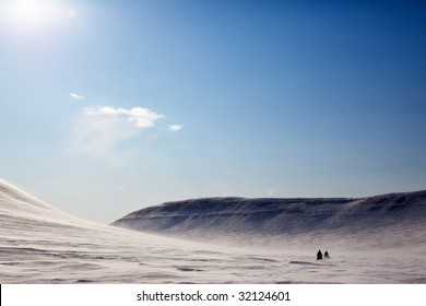 A barren winter landscape with two snowmobiles traveling across the horizon