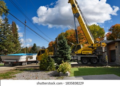 Barrie, Ontario, Canada - October 16, 2020: Crane ready to lift fiberglass swimming pool shell from flatbed truck over hydro wires and house to back yard in the Fall