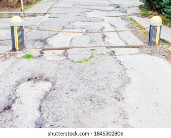 A barrier in the form of a chain stretched between two low striped posts above a road with broken asphalt