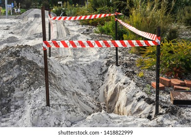 Barrier in place to stop people falling into a hole.Safety flagging on four star pickets, enclosing an excavation in sand, for site works for a residential block.