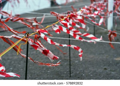Barrier tape of plastic with red and white stripes fluttering in the wind, selected focus, narrow depth of field