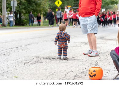 Barrington, IL/USA - 09-29-2018: Cute little boy standing in street watching the end of hometown homecoming parade