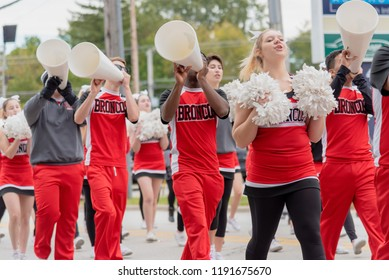 Barrington, IL/USA - 09-29-2018: High school students showing hometown school spirit marching in homecoming parade with pom poms