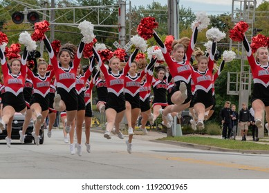 Barrington, IL/USA - 09-29-2018: High school pom pom girls showing school spirit performing in homecoming parade, jumping action shot