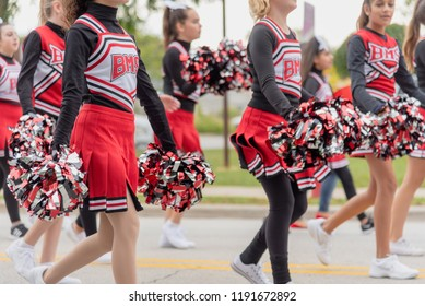 Barrington, IL/USA - 09-29-2018: Middle school girls showing hometown school spirit marching in homecoming parade with pom poms