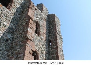 Barrow in Furness, Cumbria / England - April 19, 2019: Part of the ruined castle on Piel Island on a bright sunny day with blue sky. Lots of old stone work with medieval, arched windows.