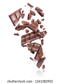 Bars of chocolate are broken in the air, isolated on white background