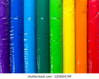 Bars of Rainbow clays or plasticines for kid's creative playing wrapped up by clear plastic of each. Colorful as purple or violet, navy, sky blue, dark green, soft or light green, yellow, orange, red