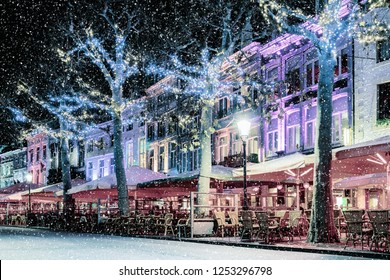 Bars and restaurants with christmas lights on the famous Vrijthof square in Maastricht during snowfall, The Netherlands
